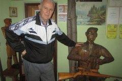 SRBAC-Dusan-Lepir-u-muzeju-pored-svog-autoportreta-lovca-od-drveta